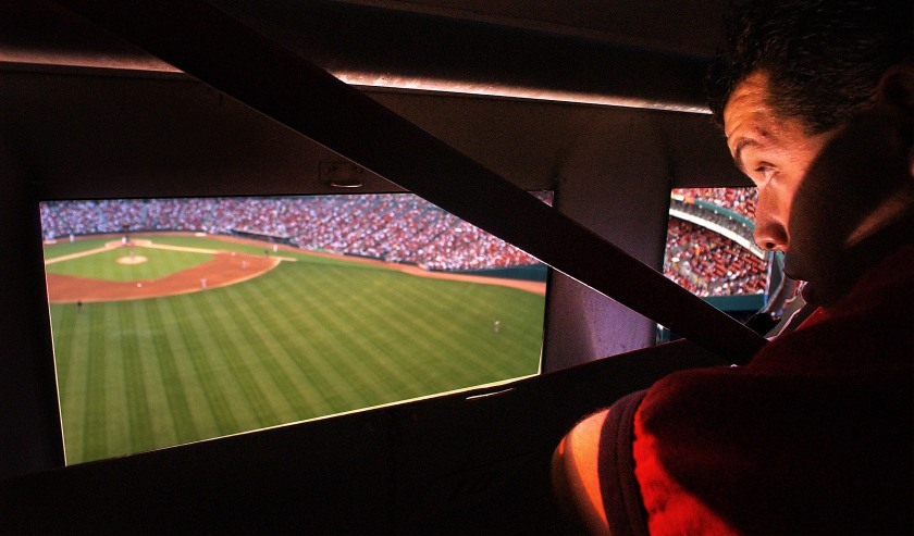 Manual Scoreboard- Peering through the ninth-inning box window, Danny Buffa, a manual scoreboard operator at Busch Stadium, takes in the Cardinals-Giants Wednesday night.